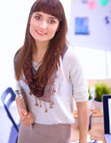 Young attractive fashion designer standing by desk in office, holding folders Stock Image