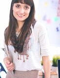 Young attractive fashion designer standing by desk in office, holding folders.  royalty free stock image