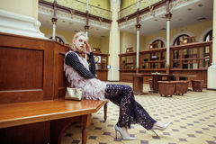 Young attractive fashion lady on railway station waiting, vintage people concept in classic interior Royalty Free Stock Images