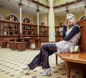 Young attractive fashion lady on railway station waiting, vintage people concept in classic interior Royalty Free Stock Image