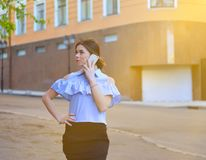 Young attractive fashion model posing on camera and talking on the phone royalty free stock images