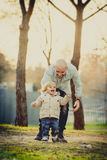 Young attractive father and little cute son playing in the park stock image