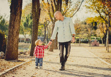 Young attractive father and little cute son playing in the park royalty free stock image