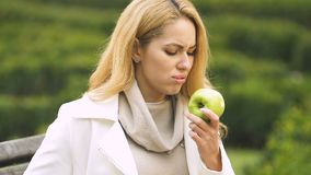 Young attractive female biting apple, feeling sick, indigestion, sensitive teeth. Stock footage stock footage