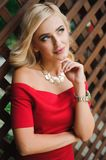 Young attractive female blonde woman in red dress sitting on chair royalty free stock images