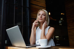 Young attractive female calling with her smart phone while sitting with portable net-book in coffee shop, Stock Photo