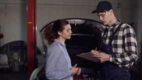 Young attractive female car owner explains to automotive technician all her complains about her vehicle and signes. Something on his notepad stock video