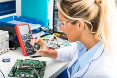 Female electronic engineer checking CPU microchip in laboratory. Young attractive female digital electronic engineer checking CPU processor microchip in Royalty Free Stock Photos