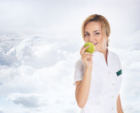 A young attractive female doctor eating an apple Stock Photo