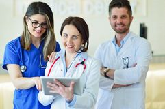 Young Attractive female doctor in front of medical group. Royalty Free Stock Photos