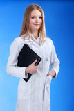 Young attractive female doctor is standing with the clipboard an. Young attractive doctor isolated over blue background Stock Images