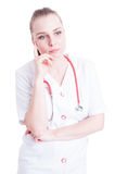 Young attractive female doctor wearing white coat and thinking Royalty Free Stock Photo