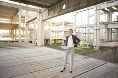 Young attractive female engineer at the construction site. Young attractive female engineer stands very satisfied with the completed construction work Royalty Free Stock Image