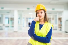 Young attractive female engineer thinking. As pensive meditating for solution to problem concept on indoor lobby building background Royalty Free Stock Photography