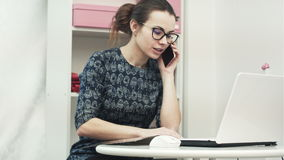 Young attractive female fashion designer using computer laptop and talking on mobile phone call in manufacturing office stock footage