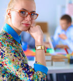 Young attractive female fashion designer working at office desk Stock Images