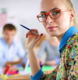 Young attractive female fashion designer working at office desk Stock Image