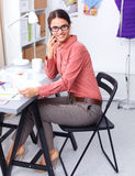 Young attractive female fashion designer working at office desk, drawing while talking on mobile Stock Images