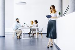 Elegant businesswoman standing in office with digital tablet Royalty Free Stock Image