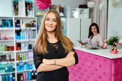 Young attractive female receptionist of beauty salon standing with hands crossed royalty free stock image