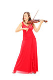 Young attractive female in red dress playing the violin Stock Photography