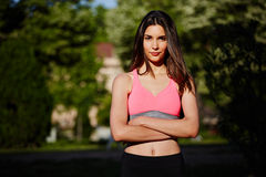 Young attractive female runner with crossed arms standing in the park on beautiful trees background. Fitness and healthily lifestyle, sport and healthy concept royalty free stock photo