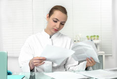 Young attractive female scientist or graduate student reads scie Stock Photo