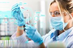 Young attractive female scientist researching in the laboratory. With futuristic scientific air interface with chemical formulas and research data in the stock photos