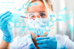 Young attractive female scientist researching in the laboratory. With futuristic scientific air interface with chemical formulas and research data in the stock photo