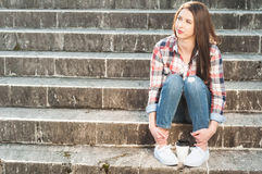 Young attractive female sitting on stairs with a coffee cup Royalty Free Stock Photography