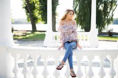 Young attractive female sitting on stone in park summer time royalty free stock photography