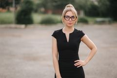 Young attractive female techer in black dress with sunglasses standing outside. Background of school stock image