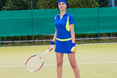 Young attractive female tennis player holding a racket and a bal Royalty Free Stock Photography