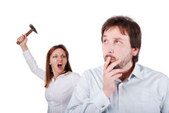 Young attractive female about to hit male. From the back with hammer Royalty Free Stock Images