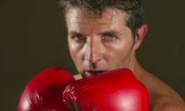 Young attractive and fierce looking man in boxing gloves posing in defense boxer stance isolated on dark background in sport and. Close up face portrait of young stock images