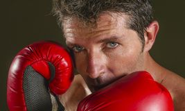 Young attractive and fierce looking man in boxing gloves posing in defense boxer stance isolated on dark background in sport and. Close up face portrait of young stock image