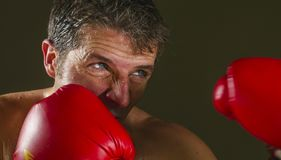 Young attractive and fierce looking man in boxing gloves posing in defense boxer stance isolated on dark background in sport and. Close up face portrait of young royalty free stock images