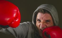 Young attractive and fierce looking man in boxing gloves throwing punch aggressive isolated on dark background in sport and. Close up face portrait of young royalty free stock photography
