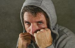Young attractive and fierce looking man wearing hoodie posing in aggressive fighter stance isolated on dark background in sport. Close up face portrait of young stock images