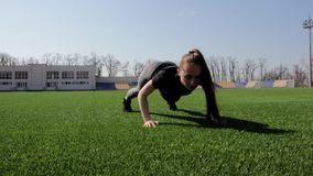 Young attractive fit active female athlete stretches muscles doing push ups warm up outdoor working out at big stadium stock video footage