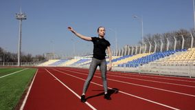 Young attractive fit active female athlete warm up stretch muscles outdoor working out outside big stadium on sunny day stock video footage