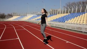 Young attractive fit active woman jumping with skipping rope working out warming up at big stadium on sunny spring day stock video footage