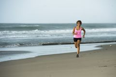 Young attractive and fit Asian sport runner woman running on beach sea side smiling happy in fitness. Body care and healthy lifestyle concept Royalty Free Stock Photos