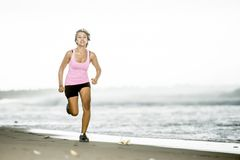Young attractive and fit Asian sport runner woman running on beach sea side smiling happy in fitness. Body care and healthy lifestyle concept Stock Photography