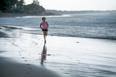 Young attractive and fit Asian sport runner woman running on beach sea side smiling happy in fitness. Body care and healthy lifestyle concept Royalty Free Stock Images