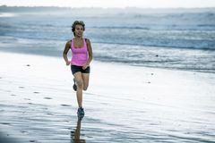 Young attractive and fit Asian sport runner woman running on beach sea side smiling happy in fitness. Body care and healthy lifestyle concept Stock Image