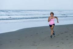 Young attractive and fit Asian sport runner woman running on beach sea side smiling happy in fitness. Body care and healthy lifestyle concept Stock Photos