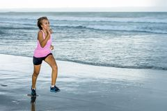 Young attractive and fit Asian sport runner woman running on beach sea side smiling happy in fitness. Body care and healthy lifestyle concept Royalty Free Stock Photo