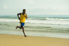 Young attractive fit athletic and strong black African American man running at the beach training hard and sprinting on sea water. In professional athlete stock photos