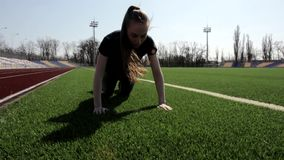 Young attractive fit female athlete does push up exercise to tone muscles, working out outdoors big stadium on sunny day stock video footage